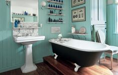 Muted turquoise beadboard complement the warm-hued wood floor and brown paint on the bath's exterior.