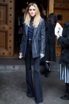 Olivia Palermo wears a tailored blazer, skinny flared denim, and a mock neck top