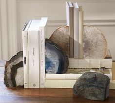 """Geode Bookends. Used as amulets in ancient times, natural agate is prized for its extraordinary stripes of vivid color. We polish these gemstones to the highest sheen to showcase their one-of-a-kind designs. Weighty and elegant, they prop up books on your desk or shelf. 8"""" wide x 10"""" deep x 12"""" high. Made of natural polished agate. Available in Blue, Green, and Natural. Set of 2. $79. 
