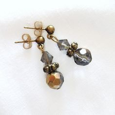 These versatile earrings consist of faceted glass beads that shimmer in shades of gold, black, bronze and gray. They include bronze spacers and gray bicone beads on bronze posts. Faceted Glass, Glass Beads, Shades Of Gold, Pearl Earrings, Drop Earrings, Bronze, Turquoise, Gray, Unique
