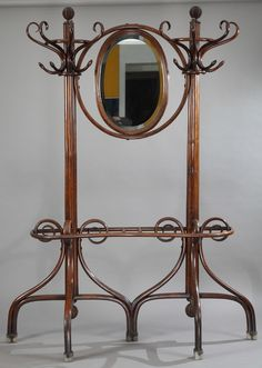 Art nouveau double coat rack by Thonet. The wooden rack is composed of two poles that have eight S-shaped hooks each. An oval mirror separates the two racks.