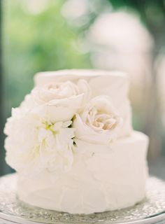 Small white two tier wedding cake decorated with some cream-toned flowers. I love how delicate and shabby chic this is! #romantic