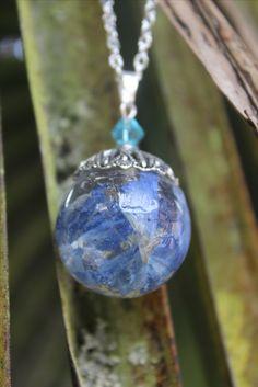 Joli collier en bulle de résine d'inclusion avec de véritables fleurs des champs cueillies et séchées par mes propres soins. Au dessus de la bulle se tiens une coupelle argentée ainsi qu'une perle cristal turquoise. Cette bulle de 2.5cm de diamètre est montée sur une chaine argentée de 80cm.