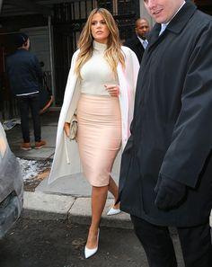 Khloe Kardashian in a turtleneck sweater, light pink skirt and crisp white cape