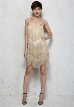 Gold Fringe Tassel Flapper Style Dress This 1920s style dress has a sheer, metallic light gold fabric with a layered tassel overlay in a zig-zag shape. This dress is fully lined and has narrow spaghetti straps. It has a V-neckline, is cut straight across the back and fastens with a back zip  ASOS £48
