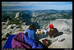 Backpackers eat breakfast, looking at Yosemite Valley from Clouds Rest. Yosemite National Park, California, USA.
