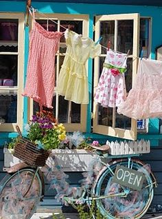 A clothesline with colorful clothes and a bike filled with flowers give this display some summer appeal! #visualmerchandising