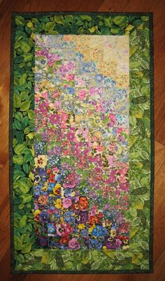 A small garden quilt, complete with two summer green borders. The top right hand corner is predominantly yellow and pale blue fabrics, and I quilted