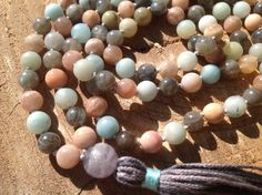 On SALE Until December 15th!     This mala is made with. Blue amazonite, grey labradorite, and glistening sunstone.  With a light purple Flourite guru bead And a charcoal grey 100% cotton tassel. Strung with silver knots on strong cord  To view other malas go here: https://www.etsy.com/your/shops/SavvyOriginals/tools/listings/section:16793253   The Sunstone is a powerful aid to bring joy and other positive feelings into your life. They have a strong so...