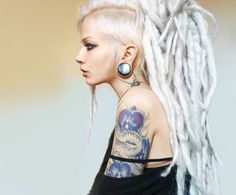 undercut with white dreadlock extensions; spider tattoo on neck; stretched lobes (woman - goth & alt)