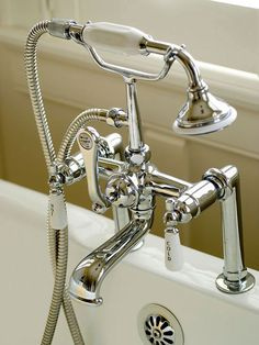 handheld shower on the bathtub provides both convenience and vintage-style good looks. The chrome faucet sparkles in the light streaming in from the windows.