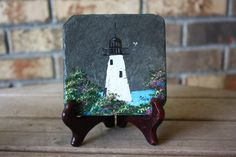 Hand painted slate tile featuring a lighthouse