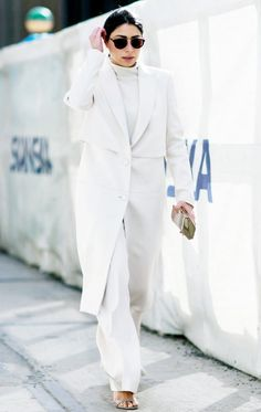 A long with coat is paired with a white sweater, white trousers and two-strap heels