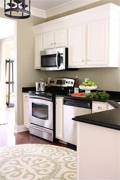 Kitchen makeover done on a budget. It looks like she painted her old cabinets and replaced her countertops, new chandlier and rug... beautiful!