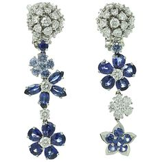 "These modern earrings from the Folie des Prés collection by Van Cleef & Arpels resemble the natural beauty of wildflowers in a delicately asymmetrical design. Made in 18k yellow gold and set with brilliant-cut round E-F VVS2-VS1 diamonds of an estimated 3.46 carats and faceted blue sapphires of an estimated 4.38 carats. An exquisite design. Measurements: 0.43"" (11mm) width, 1.69"" (43mm) length. Circa 2010s"