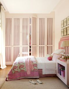 Children's bedroom in pink with paisley bed linen, vichy red and white headboard, wardrobe with pink curtains 00428826