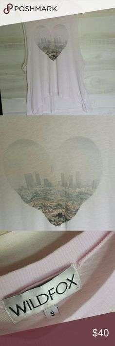 WILDFOX HEART CITY SCAPES MUSCLE TANK Ummm ladies this muscle tank though!!!! Baby light pink color with a cute heart on the front with a big city in the background of it. Size small smoke free home! Front of the shirt is shorter and it's longer in the back.  Approximately measures about 28 inches to the longest point on the front..the back measures approximately 31 inches long. The front part is a moon shaped appearance in length. Smoke free home. I ship fast & bundle. Make me an offer…