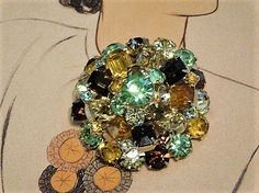 ITEM # 121644 Triple layered vintage mid century glass rhinestone brooch. Top consists of a green round faceted glass rhinestones, surrounded by 7 multiple colored round faceted glass rhinestones. Middle section consists of 9 multiple colored emerald-baguette faceted glass rhinestones with 9 small multiple colored round faceted glass accent rhinestones. Bottom section consists of 15 multiple colored round faceted glass rhinestones. All rhinestones are closed back minus the three in the…