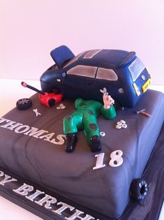 A CAR MECHANIC CAKE in the making - The brief was to have a mechanic working on a VW golf with the bonnet open. The car is a shaped madeira sponge cake as a cake topper which was placed on top along with a mechanic and car jack. July 2014