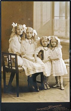Four Sisters. The eldest girl seems to be deceased. The sister on the left end has one foot braced on the floor and a firm grip on her older sister's right arm, as if she is supporting her. The next girl is holding the older girl's hand, but close inspection seems to indicate no response to the younger girl's touch. This was still very good photography.