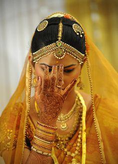 Novia india marcándose el  Bindi (tilak en idioma  hindi). Habitualmente es redondo, de color rojo o negro, hecho de cenizas o adhesivo  y se situa, al igual que los hombres, en la frente a la altura del sexto chakra (el de la sabiduría). | the perfect south indian bride