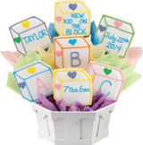 Baby Blocks Cookies. 7 cookie bouquet in a Boardwalk container. Cookies are baked fresh of sugar cookie dough and hand-decorated.