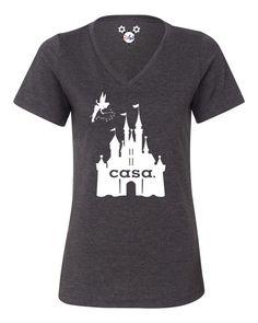 """¿Le ha dicho el mundo hoy en día lo mucho que amas de Disney? Si no es así, asegúrese de que usted no esta camiseta. Nunca hay realmente una manera perfecta de mostrar la cantidad que desea vivir en el reino mágico. Sin embargo, esta camiseta se le acerca. Hecho en el algodón más suave y con las torres llamativas del castillo, así como un polvo mágico duende aspersión, el """"Disney es mi casa"""" camiseta viene con un cuello en V y será un recordatorio encantador para planificar su próximo viaje."""