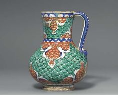 AN IZNIK POTTERY JUG  OTTOMAN TURKEY, CIRCA 1575  Of bulbous form on short foot rising to slightly flaring mouth with simple loop handle, decorated with all-over design of pairs of white split-palmettes with blue highlights forming cusped panels containing red fish-scale, against a ground of green fish-scale, the base with a register of stylized marbling, a zig-zag band of blue on white ground at the waist and a band of white and red half rosettes on blue ground at the mouth,  7in.  high
