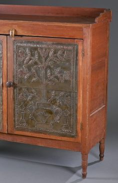 "Poplar with red wash. Likely by the Rich Brothers Family Shop, 1830 -1880.  Galleried top over two doors with tulip and flowers in urn punched tin design. Rests on turned feet.  45 1/2"" H x 52"" W x 19"" D"