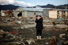 """Japan. """"A woman examines the ground where her house once stood in the town of Kesennuma, ravaged by the earthquake and tsunami of March 11. She is speaking to someone on a cell phone, but we don't need to hear her words to know what she feels."""" Photo by Carlos Barria/Reuters, """"Lens"""", New York Times"""