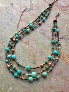 This necklace is made using three hand-beaded strands containing different…