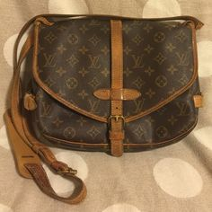 🎀make an offer! Louis Vuitton Saumur 30 authentic You're looking at a vintage Louis Vuitton Saumur 30 bag.  Clean inside, no funky smells, and well taken care of. Outside canvas monogram portion of bag is in excellent condition. Leather has a beautiful patina, but also has wear. The most major sign of wear is the long strap needs to be fixed. While it's still attached, it is barely... Debating whether to take it in to get it fixed myself because I LOVE this bag. Date code AR1910. Includes…