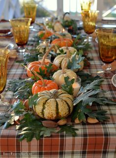 Thanksgiving table with assorted turkey plates, plaid tablecloth and easy centerpiece with pumpkins, oak leaves, nuts and votives Diy Thanksgiving Centerpieces, Pumpkin Centerpieces, Thanksgiving Tablescapes, Thanksgiving Crafts, Holiday Tables, Table Centerpieces, Christmas Tables, Pumpkin Arrangements, Centerpiece Ideas