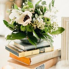 How lovely is this simplistic centerpiece? Lush floral stacked on vintage books. #RiverwoodMansion