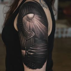 Denis Sivak black and grey spiraling staircase with light diffused arm tattoo