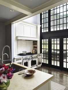Black iron factory window wall in kitchen with double height ceilings. Contrasts with traditional white cabinetry and neutral grey paint. Fantastic focal point! designed by Interior designer Barbara Bottinelli out of Philadelphia.