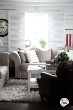 Livingroom with old wardrobe doors as shutters and rustic wood panel on walls for a Coastal Living feeling.