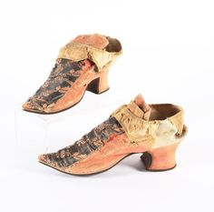 A pair of woman's shoes, mid 18th century. Pink ribbed silk with central bands down the vamps of pink silk and metal thread floral brocade, latches of ribbed silk, bound with pink silk; Louis heels and upturned toes.