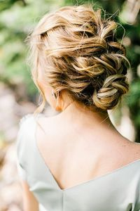 curly hair loosely French braded into a messy bun cute for a night out brides maid or even at a cocktail party