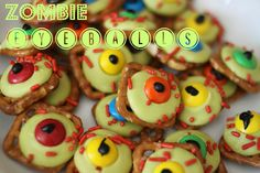 Zombie Eyeballs! Use square waffle pretzels, yellow or green candy melts, M&Ms, red sprinkles and a dot of black icing in the center! Heat the pretzels with candy melts on them just until they barely start to melt. Add sprinkles and M&Ms, then the dot of black icing. Easy, cute Halloween snacks!