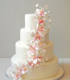 Elegant white wedding cake with pink and white flowers.