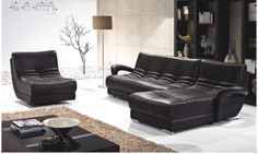 Black Leather Sofa with arms on white floor connected by brown floor lamp and beige tile wall