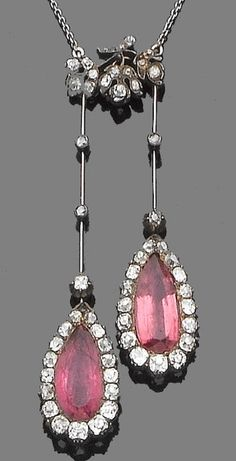 A pink tourmaline and diamond negligee pendant, circa 1900.  Each pear-shaped mixed-cut pink tourmaline within an old brilliant-cut diamond surround, suspended from articulated knife-edge bars collet-set with old brilliant-cut diamonds, to a similarly-set foliate surmount and a trace-link chain diamonds approx. 3.00ct. total, length: pendant 6.9cm., chain 46.5cm.
