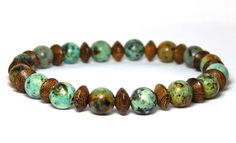 This casual mens wood and gemstone bracelet is made with 8mm African Turquoise with Robles wood. A great look for everyday. African Turquoise Properties: Helps one to express themselves with more clar