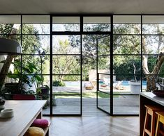 """The wall of black-steel-framed windows and doors is something Rachel was very particular about. """"The doors were custom-made in Melbourne, brought up on a truck and installed over a few days. Two things I refused to compromise on were the windows and floors, and these are the two things I'm happiest with,"""" Rachel says. #livingrooms"""