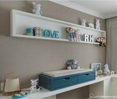 papel de parede bege com trocador de bebê azul e enxoval branco e bege, brinquedos em nicho