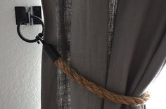 DIY rope curtain tie backs... I love the loop & hooks here. Not sure the rope goes with our home decor. Would try something else...