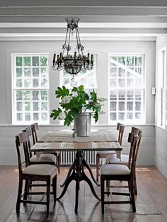 The ornate light fixture in this Connecticut farmhouse from a Paris flea market offsets the simplicty of the owner's antique farm table and chairs.   - CountryLiving.com