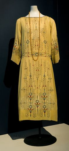 "Embroidered dress, c. 1923, House of Adair. The ""Egyptian"" color combination of yellowy-gold ground fabric with touches of blue and red embroidery suggests the aesthetic inspiration of this dress from the FIDM Museum Study Collection. Its abstract and straightforward embroidery motifs resemble a much simplified version of hieroglyphics. This dress was most likely completed at home, by a skilled embroiderer who worked from images seen in newspapers, fashion periodicals or needlework patterns."