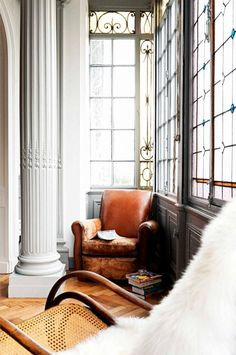 Decorative window panes and stained glass opposite large white columns, hardwood floors, and two armchairs define the space.